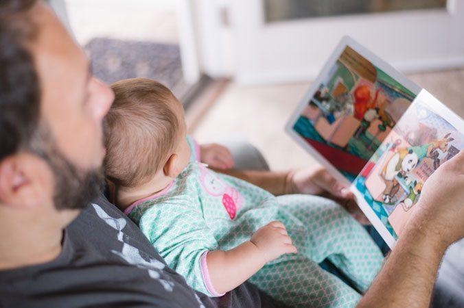 Leyendo en familia. Padre e hijo leen un libro infantil